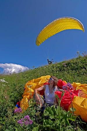 Parawaiting und Startbetrieb auf einer Alp in der Schweiz. Gleitschirme taugen auch als Wolldecke